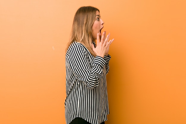 壁に対する若い本物のカリスマ的な実在の女性は大声で叫び、目を開いたままにして手が緊張します。