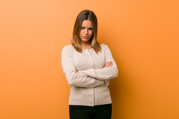 Young authentic charismatic real people woman against a wall frowning face in displeasure, keeps arms folded.