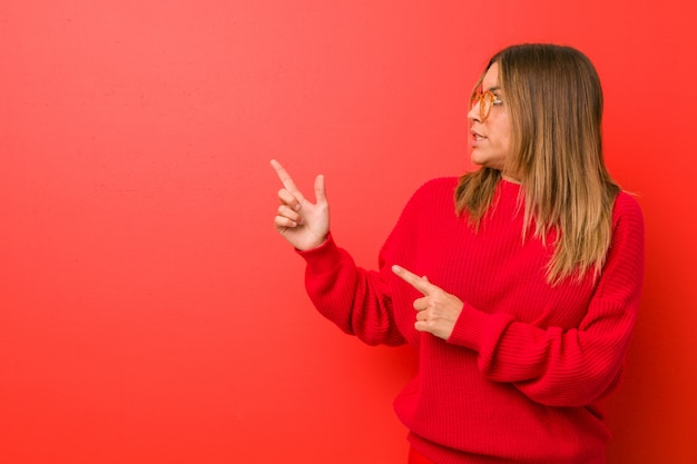 Young authentic charismatic real people woman against a wall shocked pointing with index fingers to a blank space.