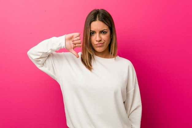Young authentic charismatic real people woman against a wall showing a dislike gesture, thumbs down. disagreement concept.