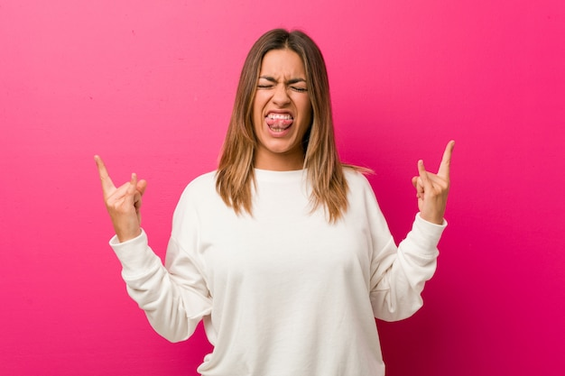 Young authentic charismatic real people woman against a wall showing rock gesture with fingers