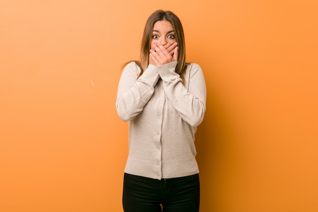 Young authentic charismatic woman shocked covering mouth with hands