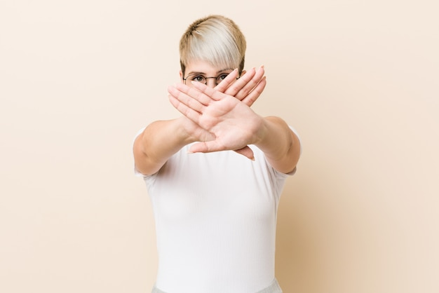 Young authentic natural woman wearing a white shirt doing a denial gesture