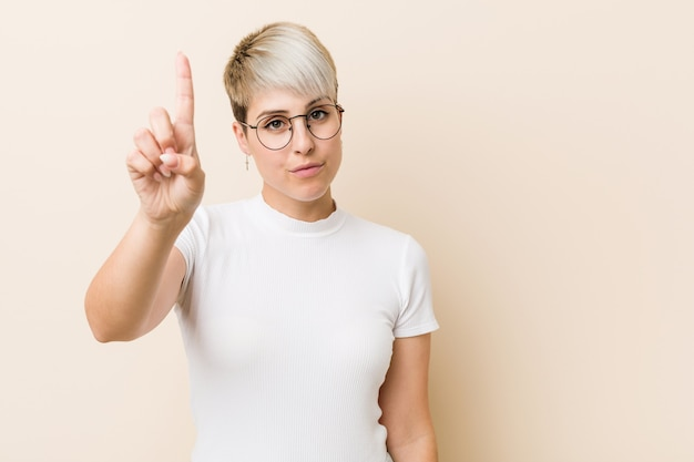 Young authentic natural woman wearing a white shirt showing number one with finger.