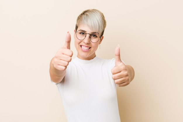 Young authentic natural woman wearing a white shirt with thumbs ups, cheers about something, support and respect concept.