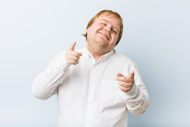 Young authentic redhead fat man cheerful smiles pointing to front.