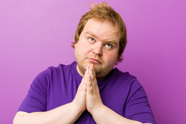 Young authentic redhead fat man holding hands in pray near mouth, feels confident.