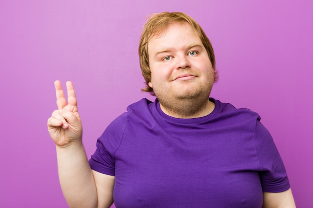 Young authentic redhead fat man joyful and carefree showing a peace symbol with fingers.