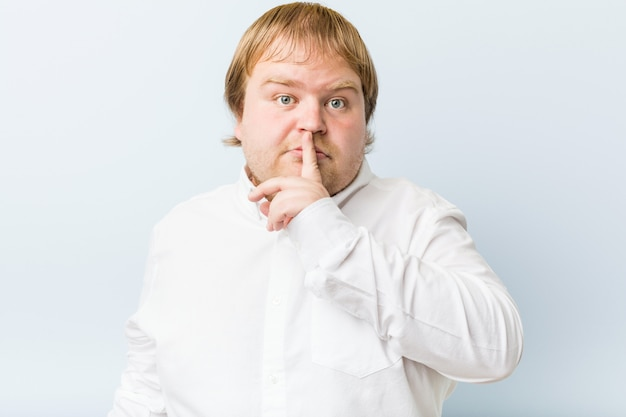 Young authentic redhead fat man keeping a secret or asking for silence.