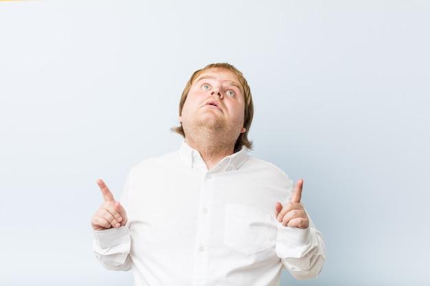 열린 된 입으로 거꾸로 가리키는 젊은 정통 빨간 머리 뚱뚱한 남자.