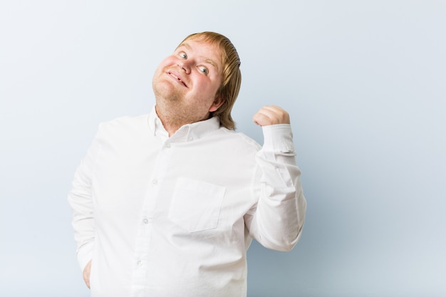 Young authentic redhead fat man points with thumb finger away, laughing and carefree.