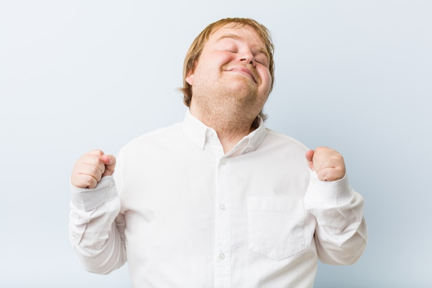 Young authentic redhead fat man raising fist, feeling happy and successful. victory concept.