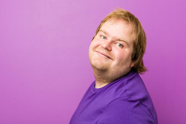 若い本格的な赤毛のデブ男はリラックスして幸せな笑い、首を伸ばして歯を見せています。