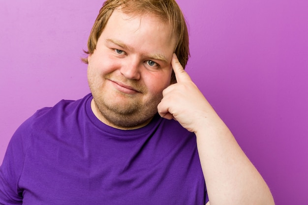Young authentic redhead fat man showing a disappointment gesture with forefinger.