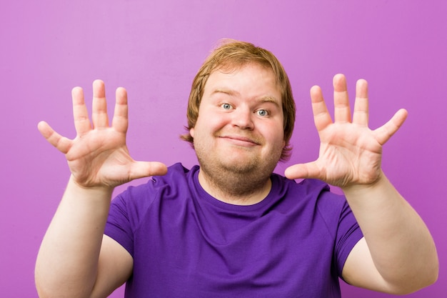 Young authentic redhead fat man showing number ten with hands.