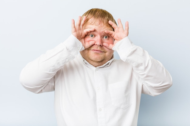 Young authentic redhead fat man showing okay sign over eyes