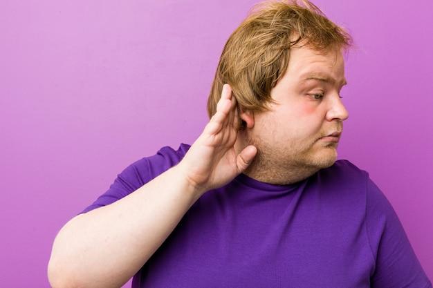 Молодой подлинный рыжий толстый человек пытается слушать сплетни.