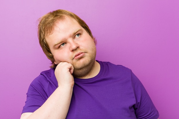 Young authentic redhead fat man who feels sad and pensive, looking at copy space.