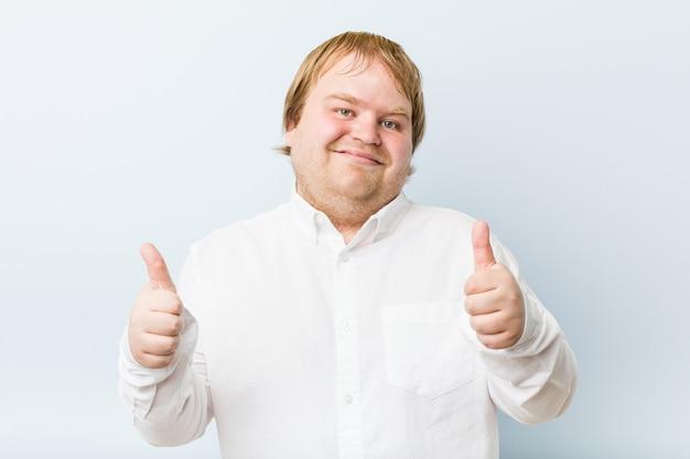 親指を持つ若い本物の赤毛のデブ男、何かについて歓声、サポートと尊重の概念。