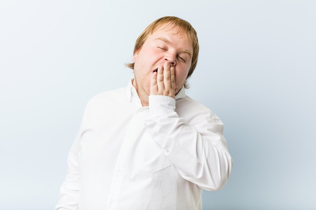 Young authentic redhead fat man yawning showing a tired gesture coning mouth with hand.