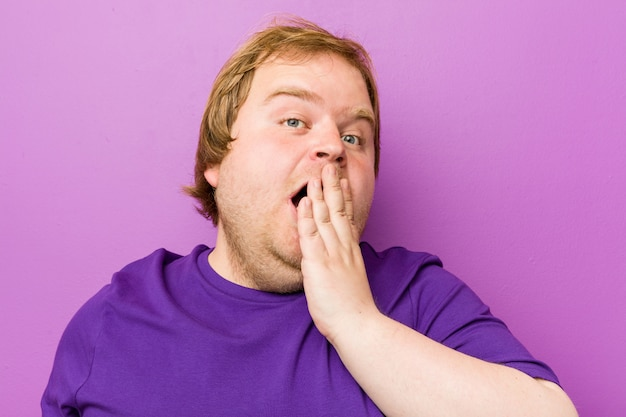 Young authentic redhead fat man yawning showing a tired gesture covering mouth with hand.
