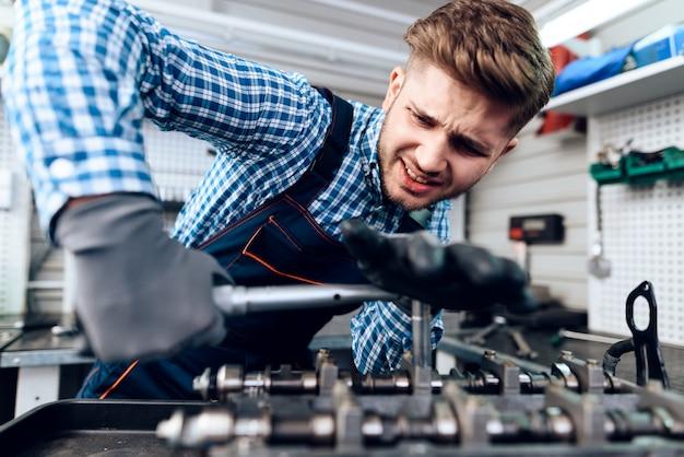 Young auto mechanic twists a nut. service station.