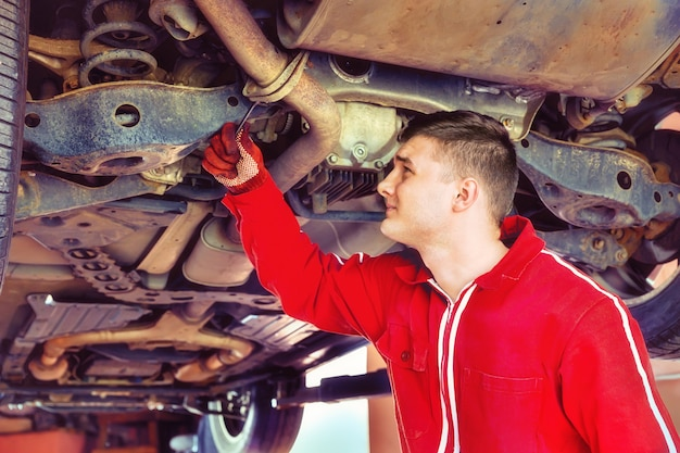 Young auto mechanic in uniform working underneath a lifted car
