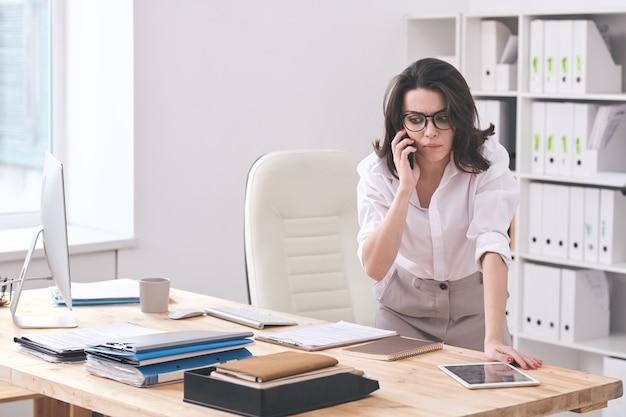 書類、タブレット、コンピューターを持って机をかがめながら、クライアントの1人と携帯電話で話している若いビジネス秘書