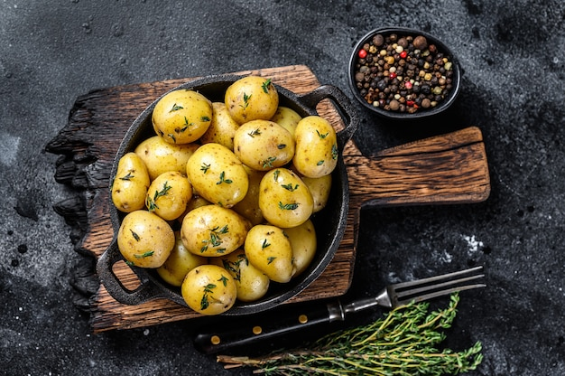 Young baby boiled potato with butter in a pan. black background. top view.