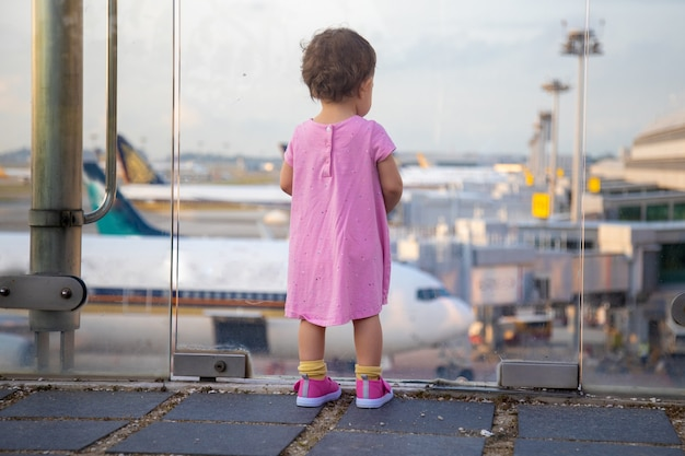 Young baby infant passanger looks at airplanes at the airport. back view.