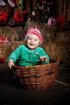 Young baby wearing a cute outfit posing for portraits in the studio sitting inside a basket with a blanket