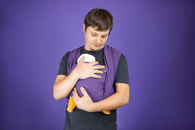 スリングフロントラップクロスキャリーで若いベビースリングの父と赤ちゃんは彼の赤ちゃんを抱きしめます