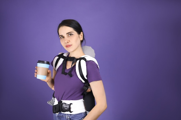 Young babywearing mother and baby in baby sling, paper cup in hand. free hand babywearing concept.