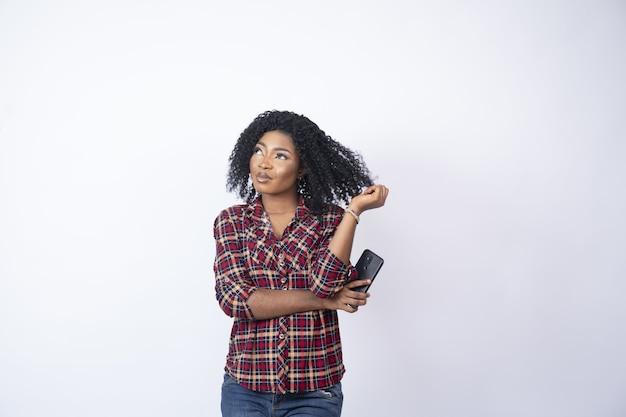 彼女の電話を保持し、何かを考えている若い背中の女性