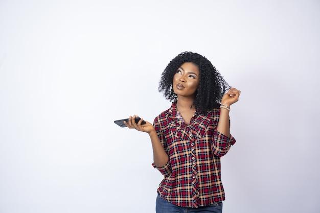 Молодая женщина спиной держит свой телефон и закручивает конец ее волос