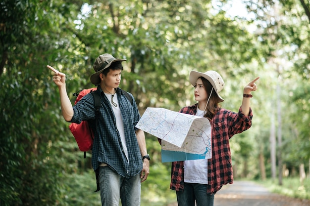 Young backpacker couple wearing hat and holding paper map are arguing about direction of forest trail.