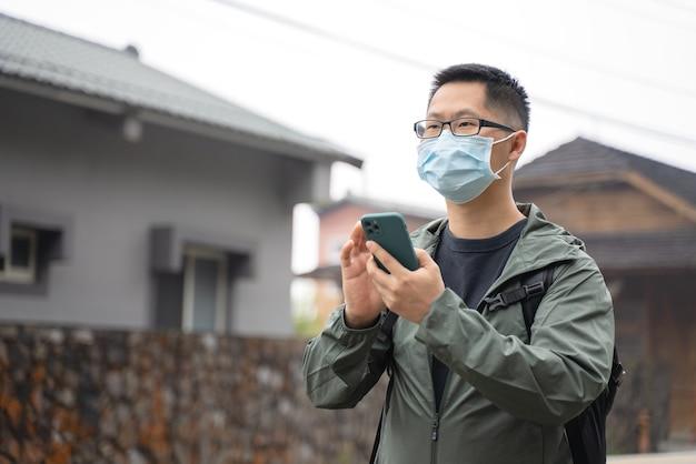 Young backpacker man is traveling alone and using smart phone to find a way with wearing mask, glasses