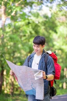 지도를 들고 있는 젊은 배낭여행자, 그는 여름방학 동안 숲속 재판에서 야외에서 휴식을 취하는 동안 큰 배낭을 메고 공간을 복사합니다.