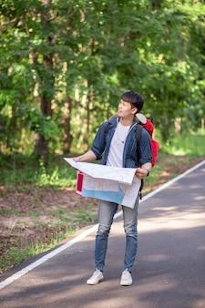 地図を持つ若いバックパッカーの男の旅行者、彼は森林試験、コピースペースで夏休みに屋外でリラックスしながら大きなバックパックを運ぶ
