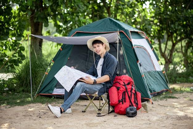 모자를 쓴 젊은 배낭 여행자는 자연 숲의 텐트 앞에 앉아 숲길의 종이 지도를 보고 여름 방학 동안 캠핑 여행을 계획하고 공간을 복사합니다.