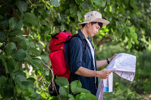 방향을 확인하기 위해 지도가 있는 모자를 쓴 젊은 배낭여행자, 그는 여름방학 동안 숲에서 휴식을 취하는 동안 큰 배낭을 메고 공간을 복사합니다.