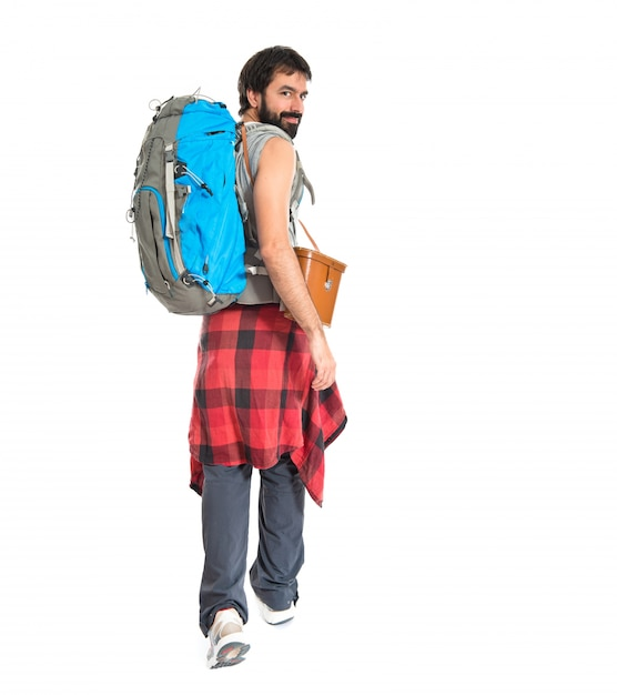 Young backpacker walking over white background