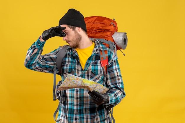 Giovane zaino in spalla con cappello nero che si tiene il naso e mappa di viaggio