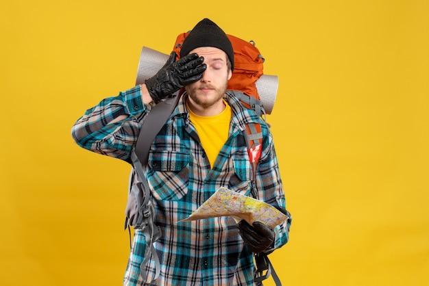 手で目を覆っている地図を保持している黒い帽子を持つ若いバックパッカー
