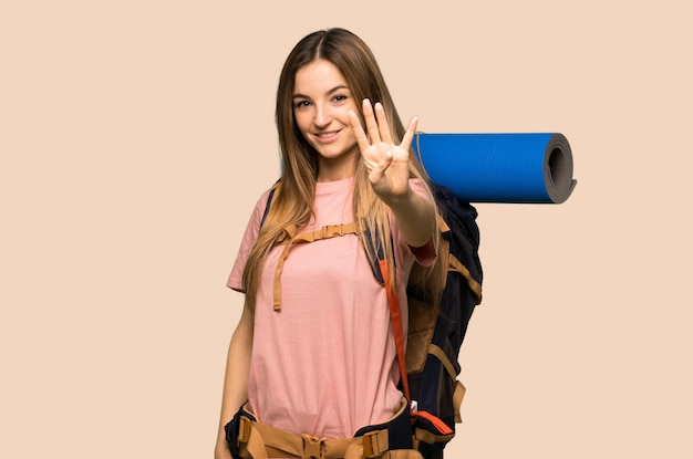 Young backpacker woman happy and counting four with fingers on isolated yellow background