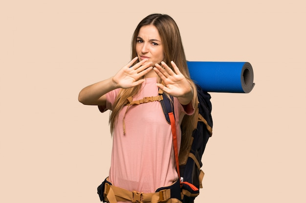 Young backpacker woman is a little bit nervous and scared stretching hands to the front