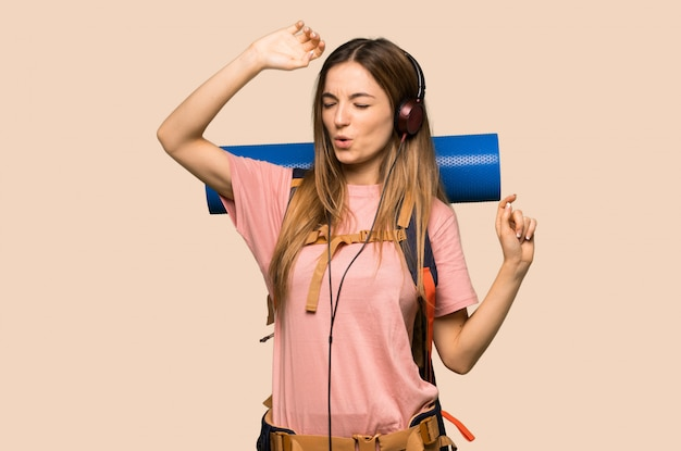 Young backpacker woman listening to music with headphones and dancing on isolated yellow background