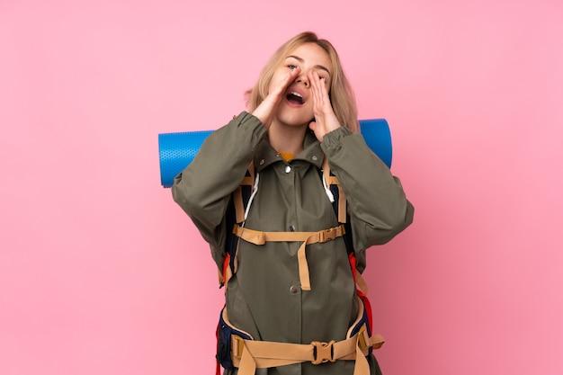 Молодая женщина рюкзаком над изолированной стеной