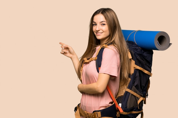 Young backpacker woman pointing finger to the side in lateral position