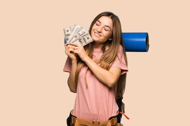 Young backpacker woman taking a lot of money on isolated yellow background